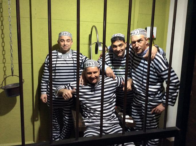 tým lidí, oblečených jako vězni, hrající únikovku